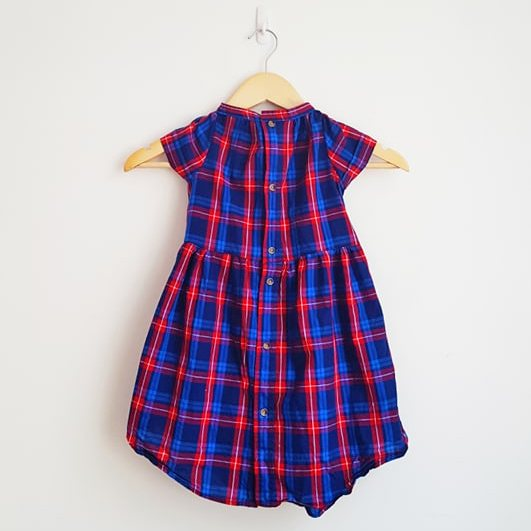 A bright blue and red check print collared girl's dress on a hanger against a white wall.
