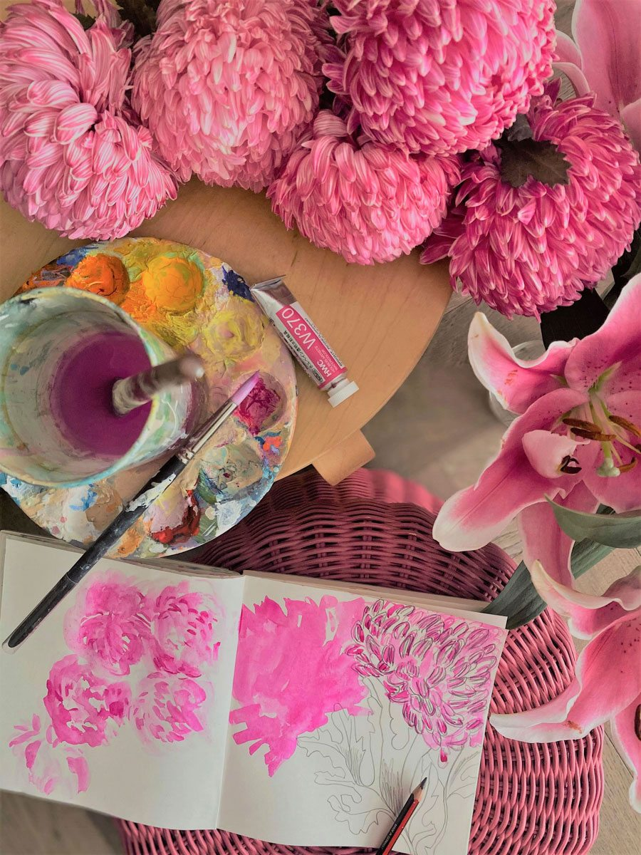 A botanical painting in progress in the HoneyBrush studio, surrounded by bold pink blooms that inspired the work