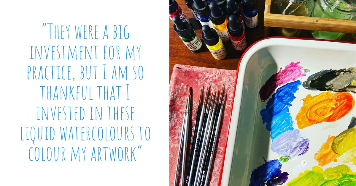 A tray of vibrant watercolours and paintbrushes on a wooden desk; 'They were a big investment for my practice, but I am so thankful that I invested in these liquid watercolours to colour my artwork'