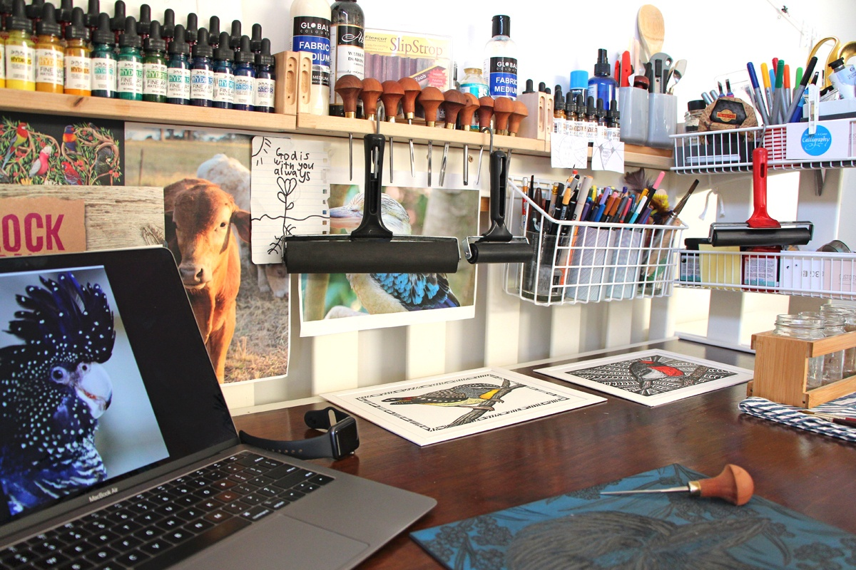The busy desk of Handmade by Hemmings sports a laptop, a linocut in progress, a number of lino prints, animal images for inspiration and a vast collection of tools and paints.