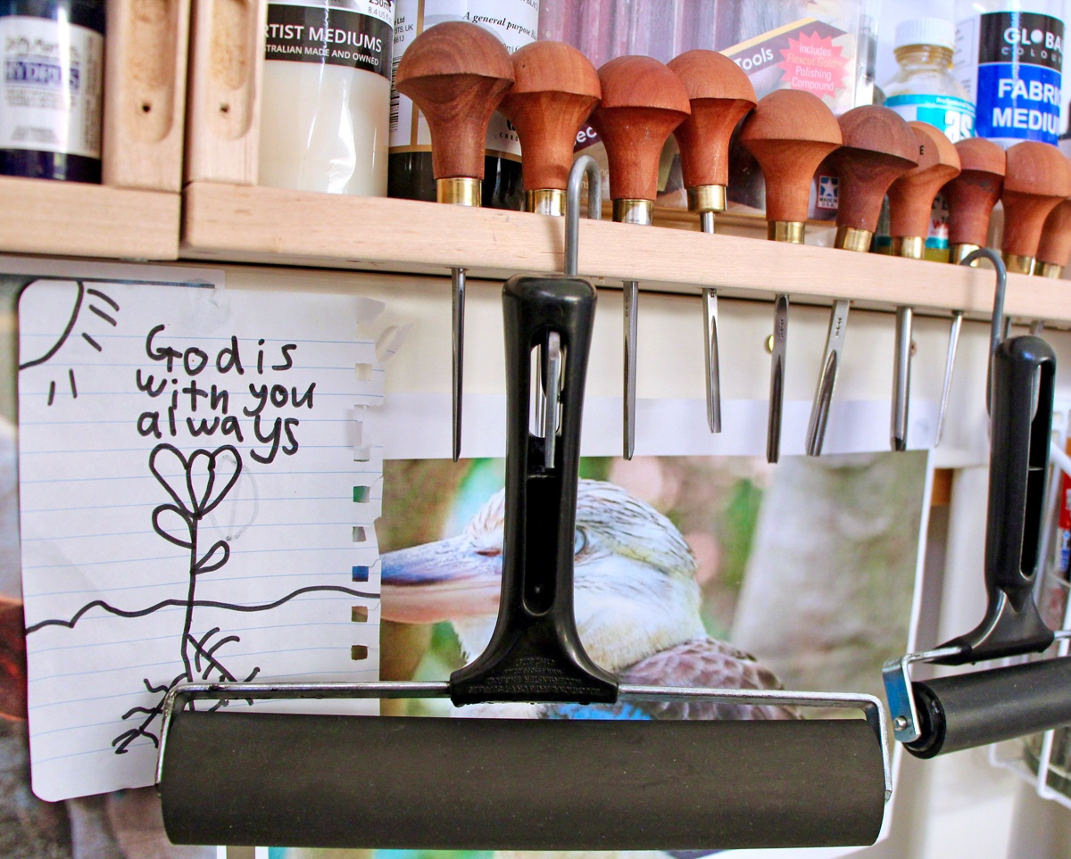 A handwritten note: 'God is always with you' hanging with the rollers and lino cutting tools of Sarah's home workspace
