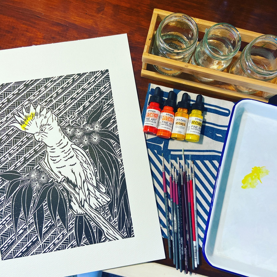 A Handmade by Hemmings linoprint of a sulphur crested cockatoo in the process of being hand-coloured with watercolours.