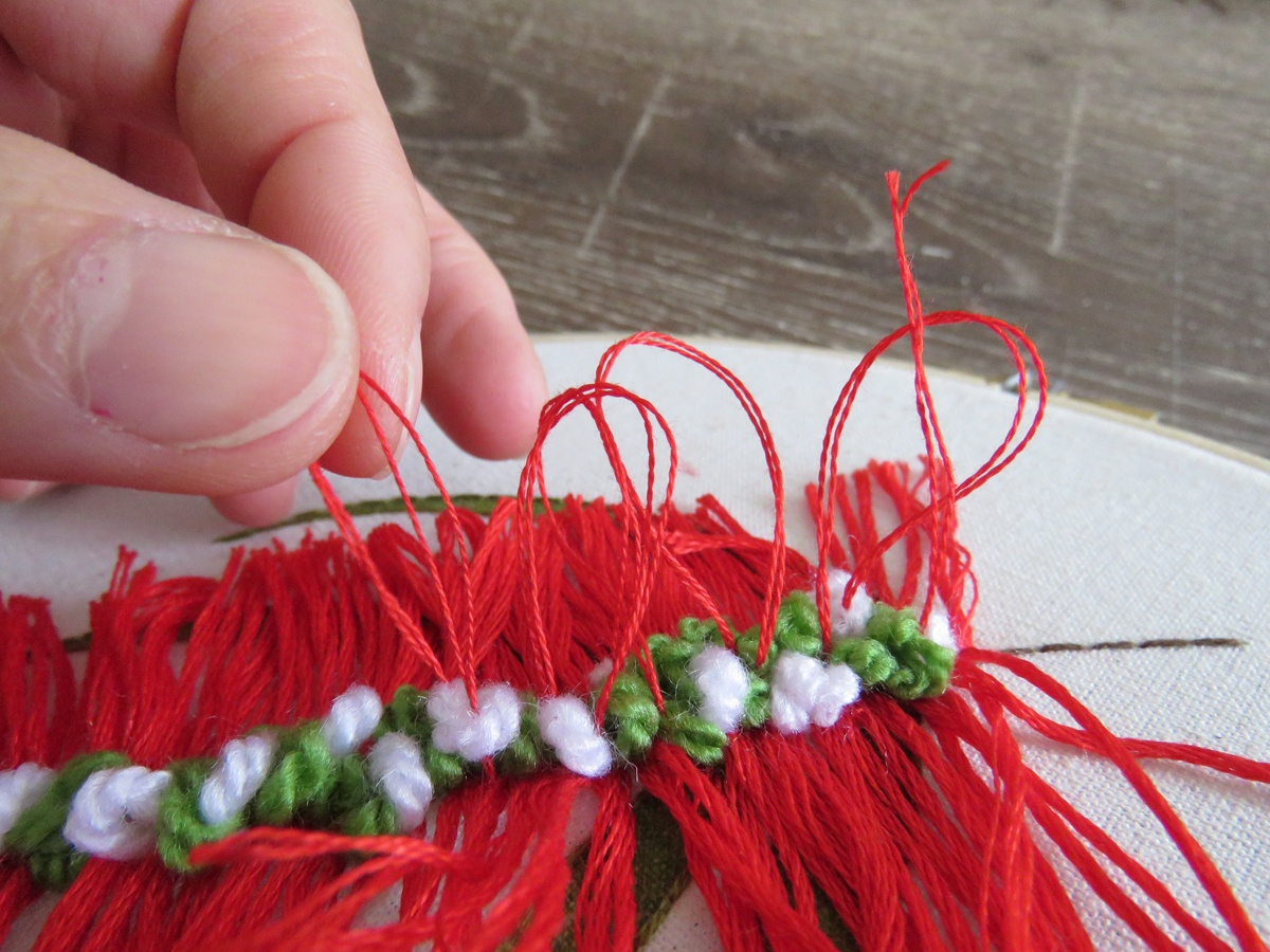 Closeup view of Jo pulling threads to create 3 dimensional texture in an Australian bottlebrush botanical embroidery design.