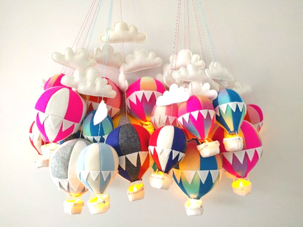 A cluster of whimsical hanging felt hot-air balloon nightlights by House Of Indie