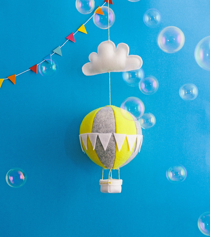Bubbles float pas a whimsical felt hot-air balloon nightlight against a backdrop of blue