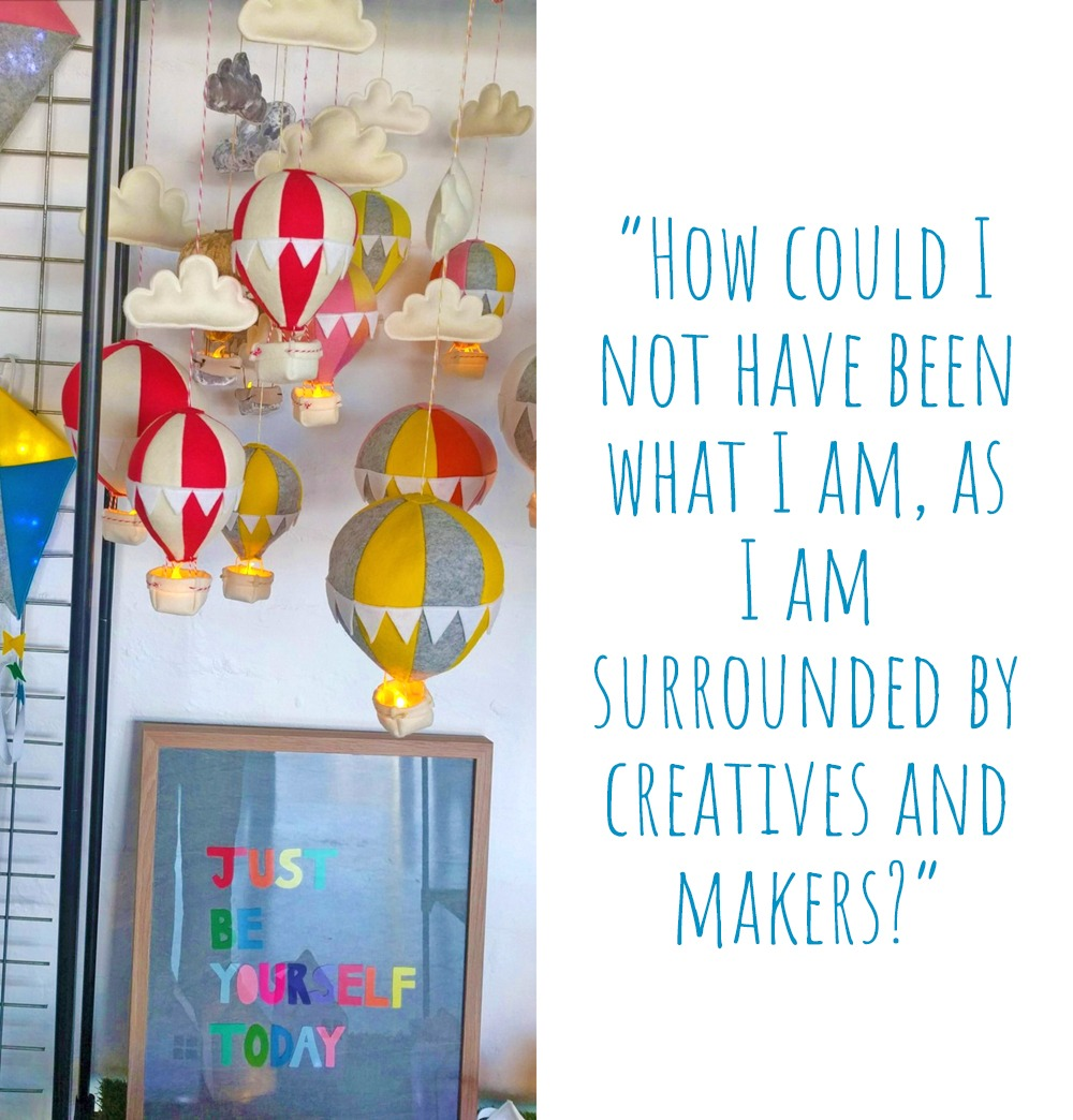 A collection of felt kites and hot air balloon night lights hang above a colourful 'Just be yourself today' framed image: 'How could I not have been what I am, as I am surrounded by creatives and makers?'
