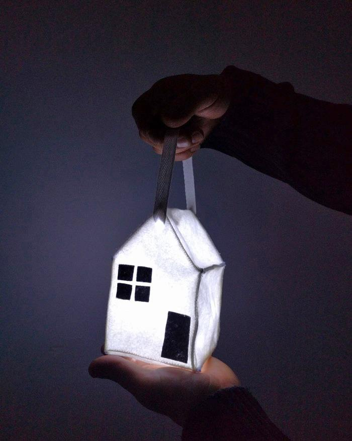 A white felt house nightlight aglow in a darkened room