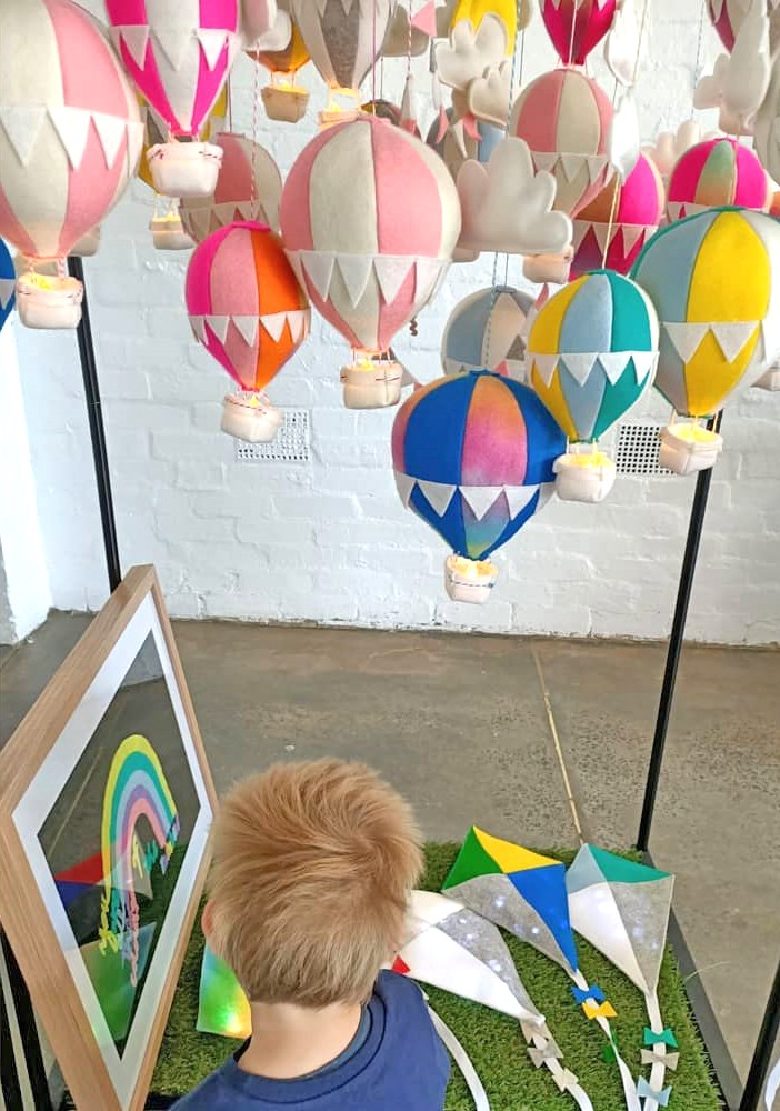 A little boy examines a display of felt kite nightlights under a hanging cluster of whimsical felt hot-air balloon nightlights at a weekend market
