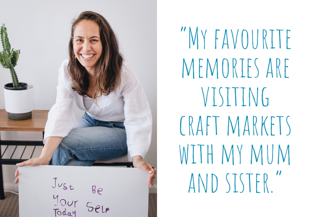 A smiling Georgina in her light-filled home, holding a hand-written sign saying 'Just Be Your Self Today'. 'My favourite memories are visiting craft markets with my mum and sister'