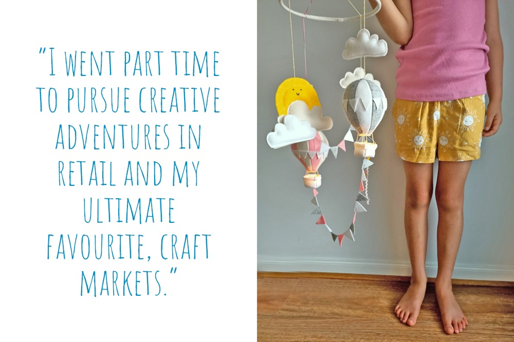 Georgina's daughter and House Of Indie namesake holding a mobile of felt clouds, sun, hot air balloon nightlights and mini bunting: 'I went part time to pursue creative adventures in retail and my ultimate favourite, craft markets.'
