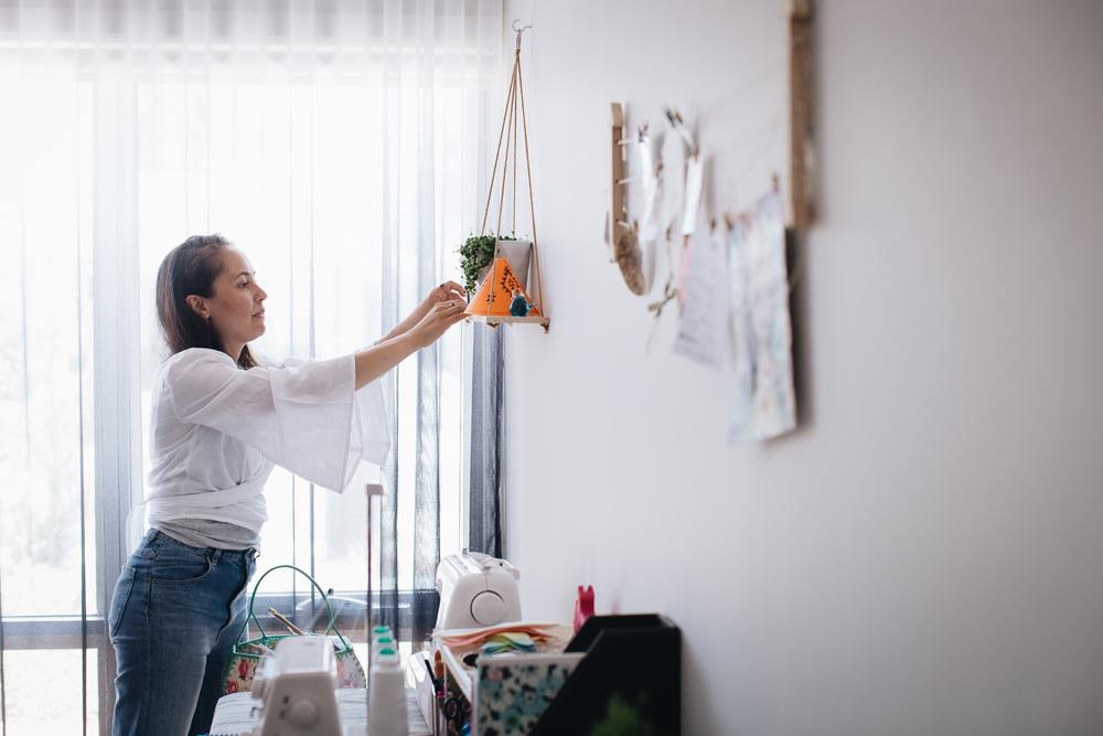 Georgina in her light-filled Melbourne home workspace arranging some of her felt creations on a hanging shelf