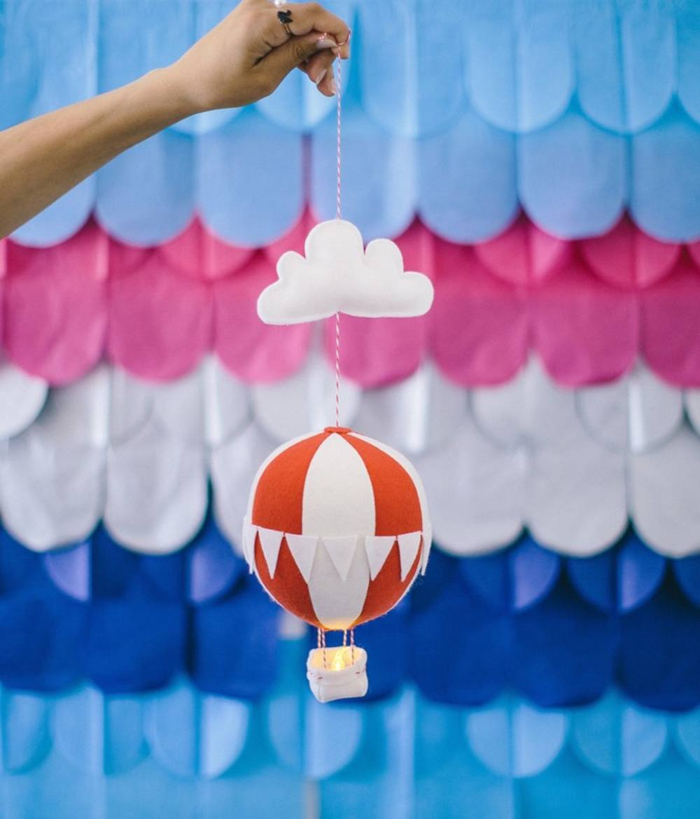 A handmade felt cloud and hot-air balloon nightlight held in front of a colourful backdrop