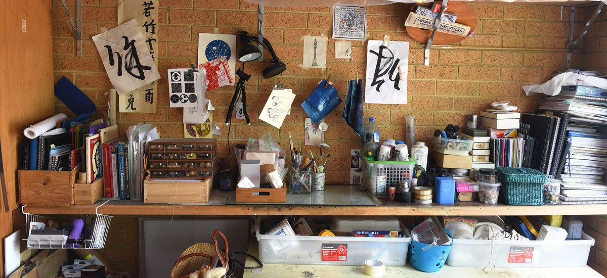 Tools of the trade; Teresa's garage wall is lined with shelves or art supplies, pottery and etching tools, and snippets oriental lettering and imagery that inspires her creative work'