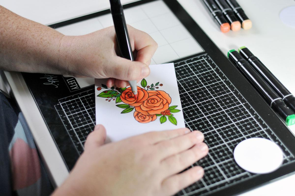 Kelly at work in her home studio, drawing a floral design to add to one of her handmade greating cards