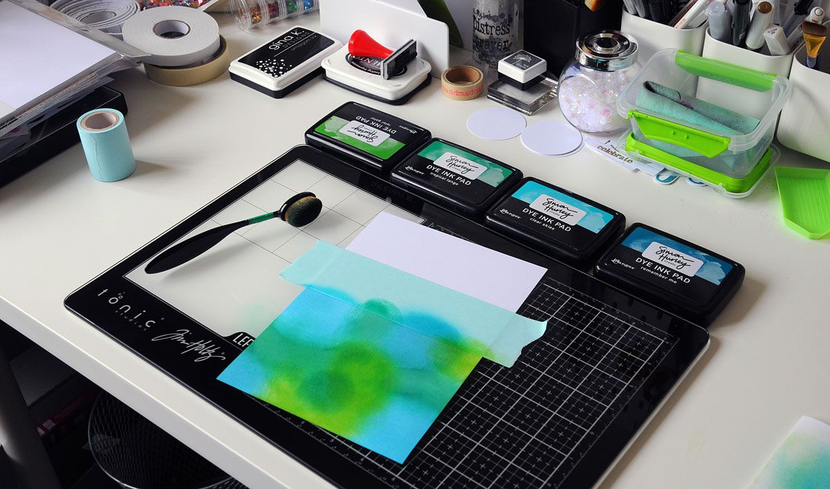 A bright blue and green sponged-ink background being applied to cardstock to form the basis of a new greeting card