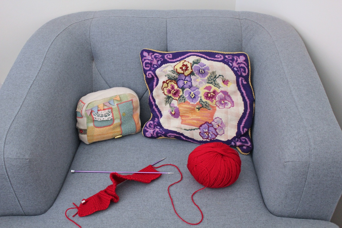 Karen's comfy crafty corner: a cosy lounge and knitting project in progress, with the caravan cushion a nod to Karen's love for travel