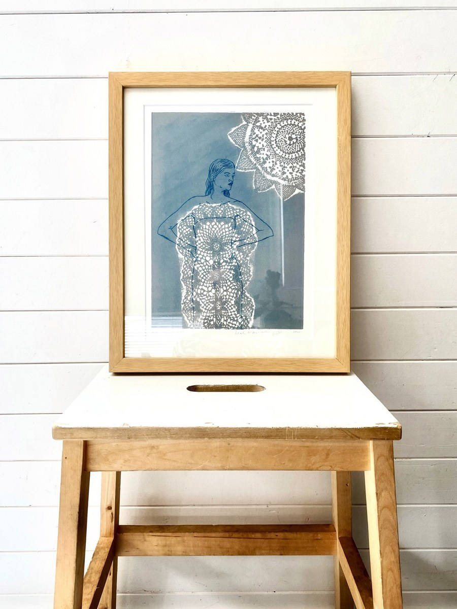 A framed print of Leah Mariani's 'Grey Star' perched on a wooden stool