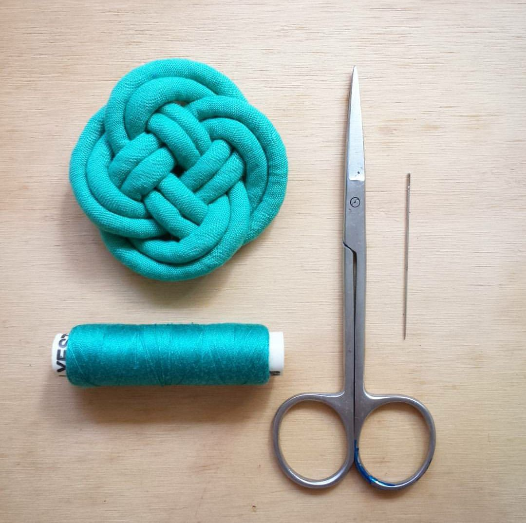 Teal fabric infinity knot with matching thread, scissors and needle