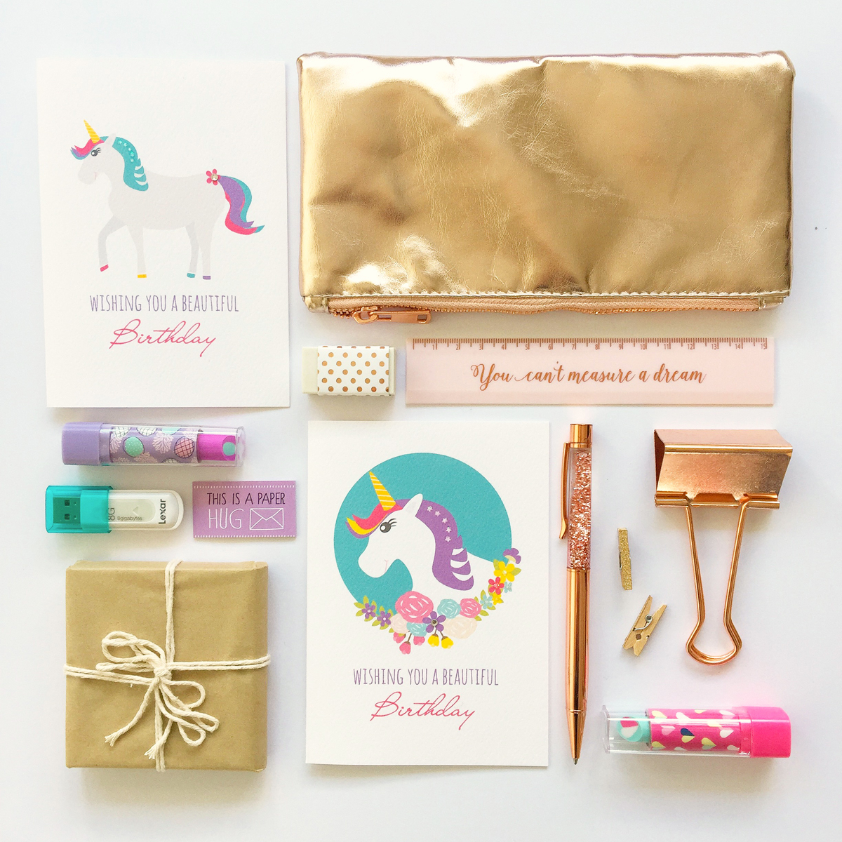 A flat-lay of Katrina's unicorn designs with a range pink and gold stationery