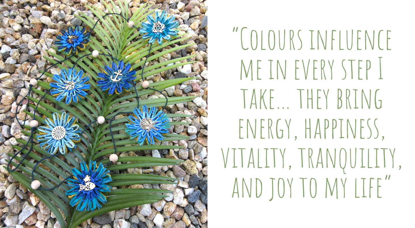 a sea-themed paper flower garland in shades of blue laid out on a palm frond and a bed of rocks; 'Colours influence me in every step I take… they bring energy, happiness, vitality, tranquillity, and joy to my life'