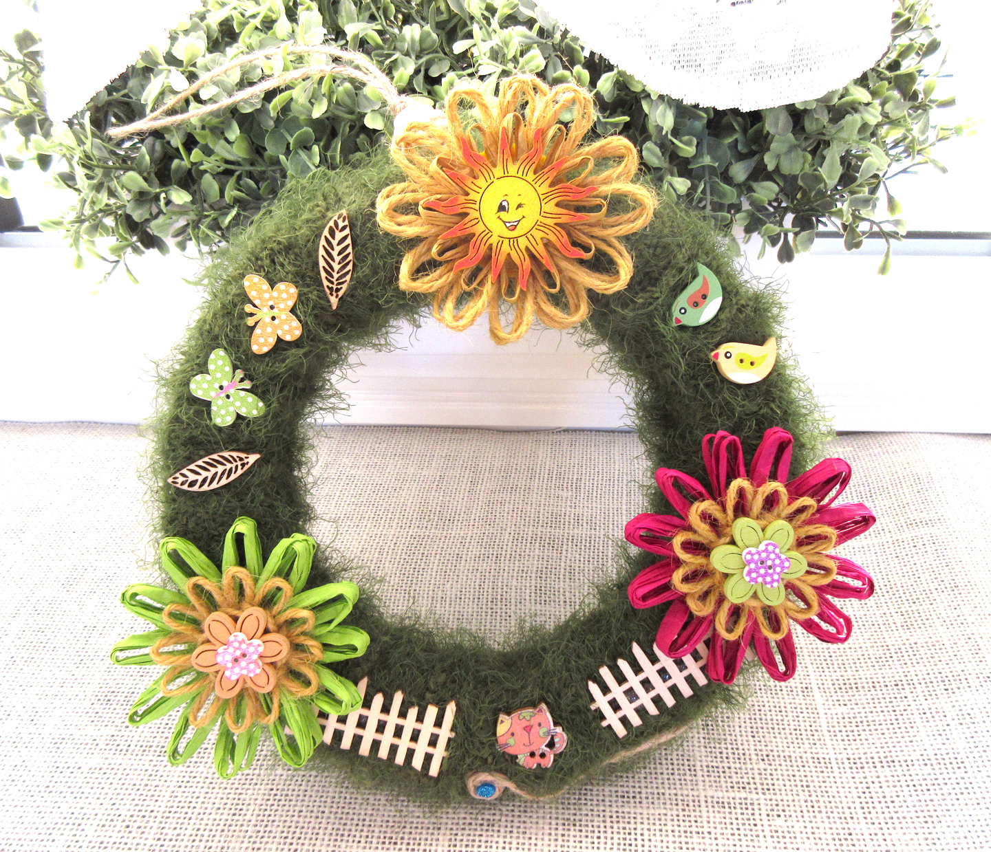 A colourful, happy artificial wreath decorated in paper and twine flowers and cheerful buttons