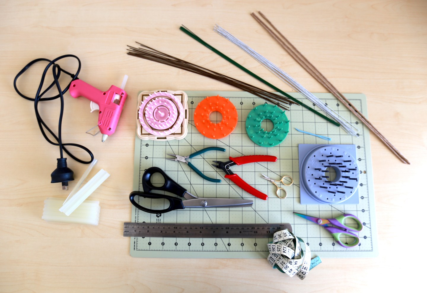 Flower-making tools; wire, pliers, scissors, hot glue gun, measuring tape, and mini looms in various sizes