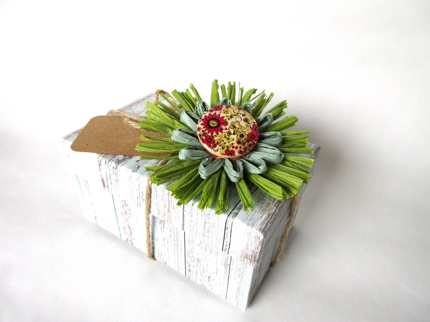 Gift wrapped box tied with string and a green and handmade red raffia flower made M Decor Botanica'