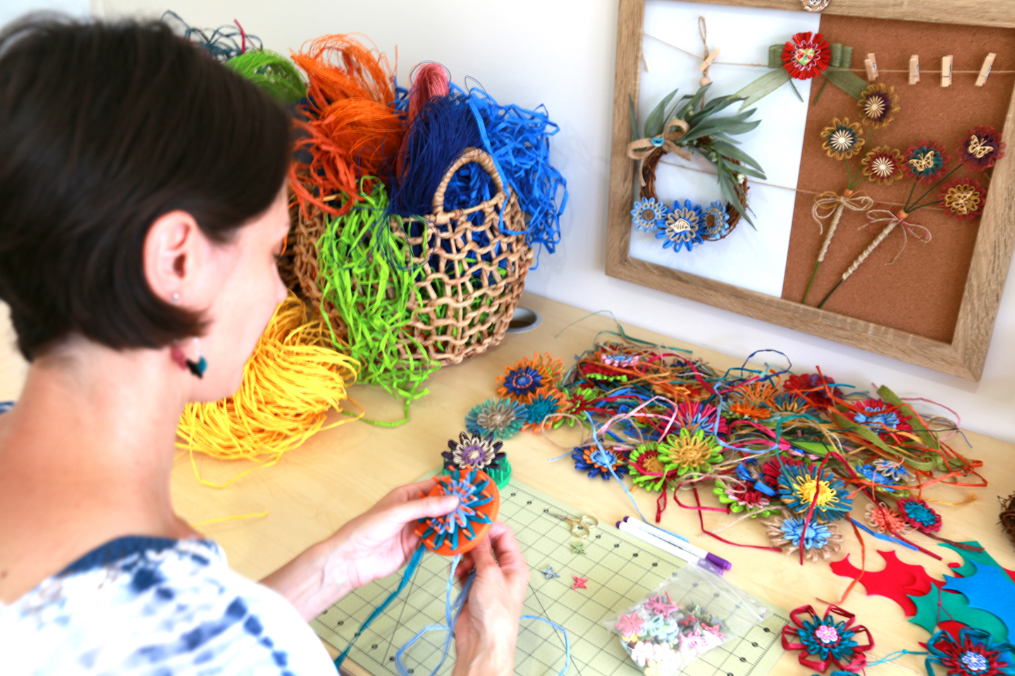 Looking over Marketa's shoulder as she weaves a raffia flower to make a floral garland decorations in her home workspace in North Queensland
