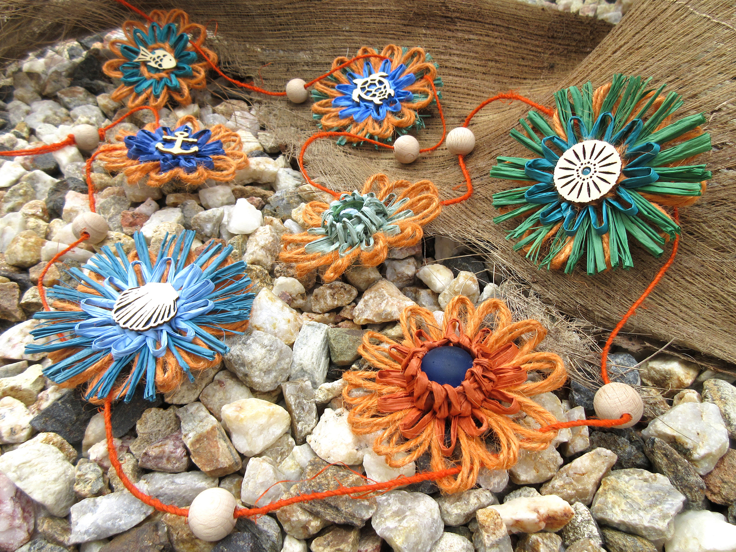 Blue, green and orange flower garland handmade by Marketa of M Decor Botanica from natural fibres like jute twine, hemp twine, raffia, paper raffia, paper string, and wool felt