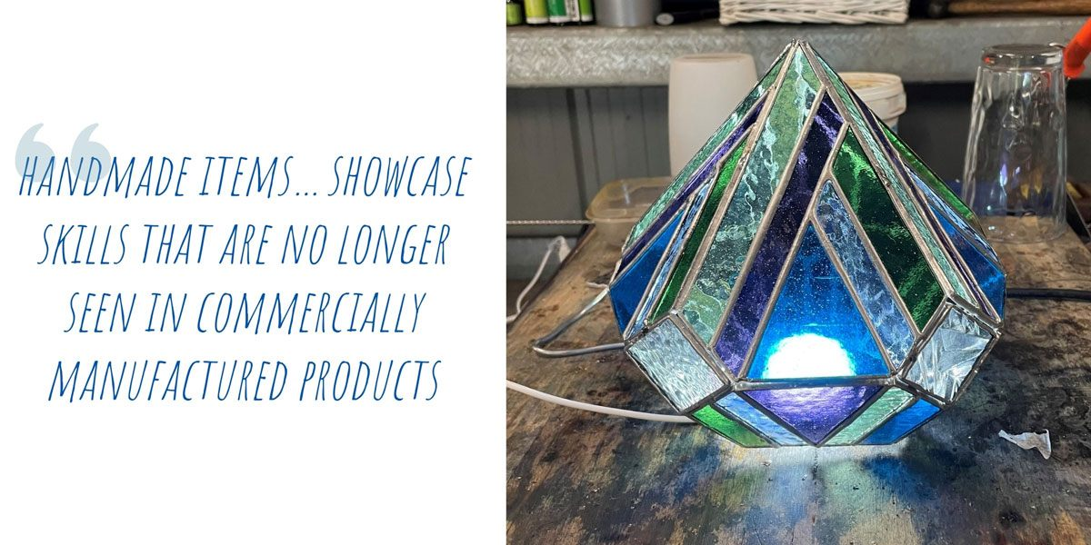 Testing a completed stained-glass lamp in the workshop; 'Handmade items…showcase skills that are no longer seen in commercially manufactured products'