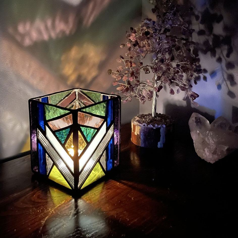 A completed 'Geo' stained-glass candle holder projects colourful dancing lights onto the wall behind