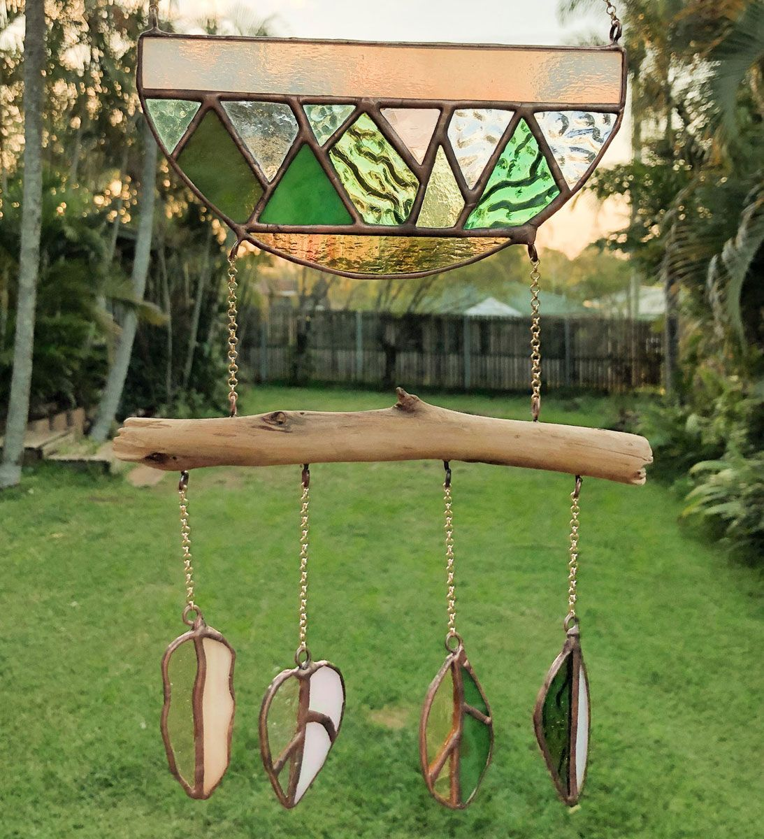 A mountain and forest themed stain glass wind chime / sun catcher in the late afternoon QLD sun