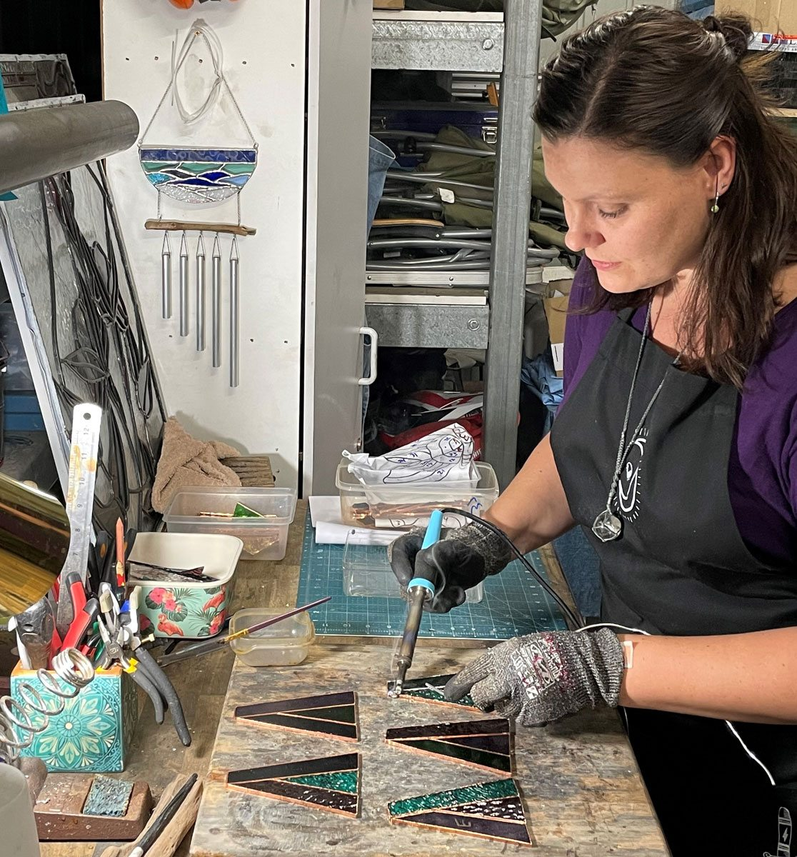 Kahleah at work on a stained-glass project in her home workspace