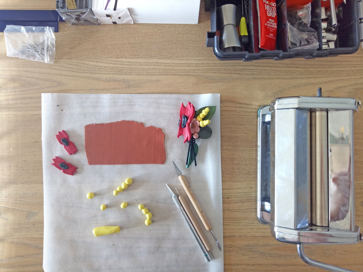 Tools of the trade: polymer clay floral arrangements in progress with cutting, shaping, and rolling tools