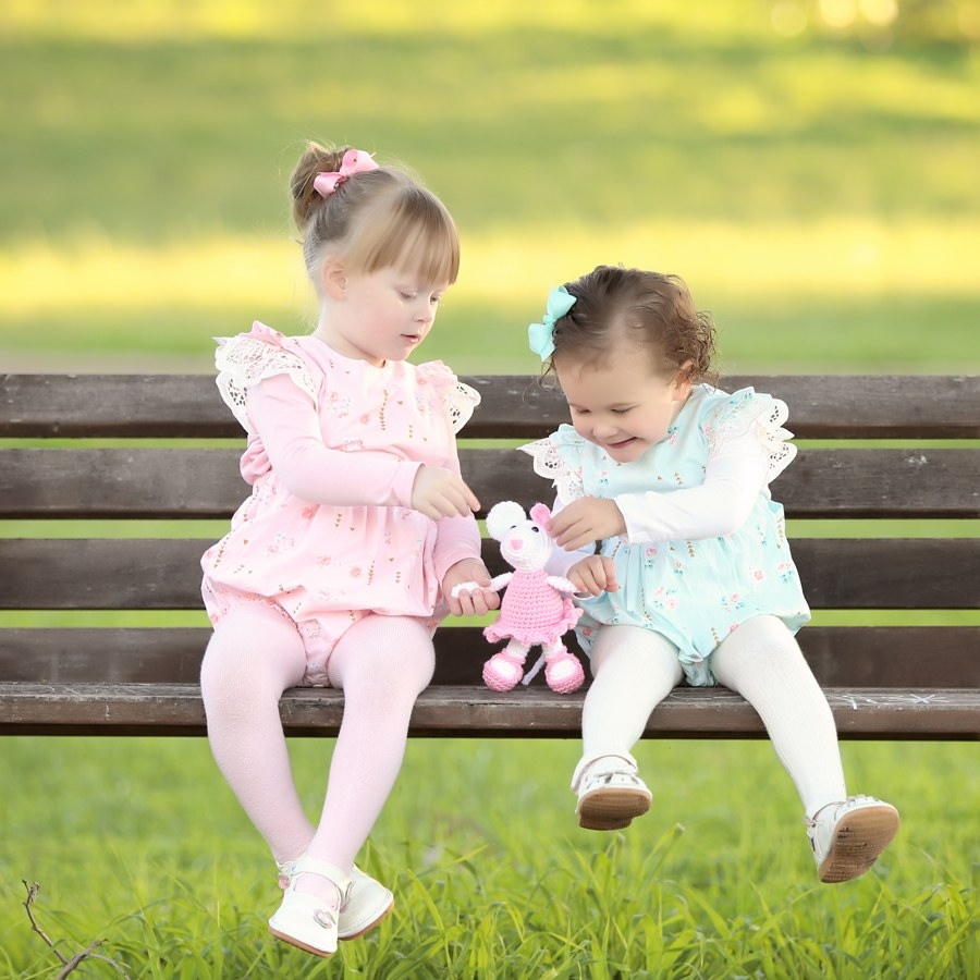 Two little girls play with one of Muriel's crochet creations on a park bench as part of a photo shoort