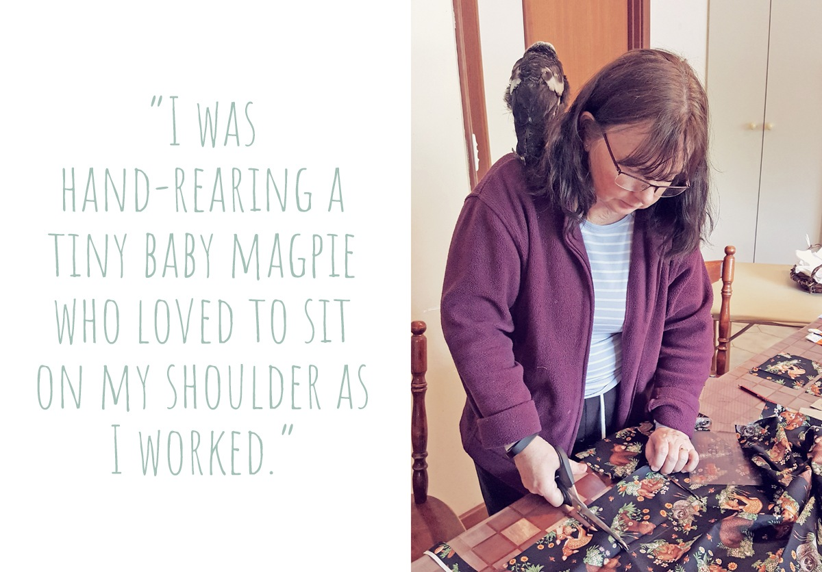 "Karen at work cutting fabric last year, with a baby magpie on her shoulder: ""I was hand-rearing a tiny baby magpie who loved to sit on my shoulder as I worked."""