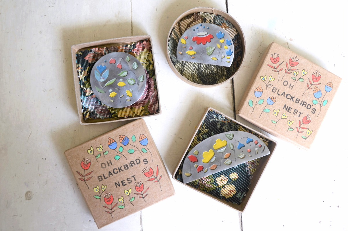 Metal brooches depicting garden scenes, boxed and almost ready to ship to new owners