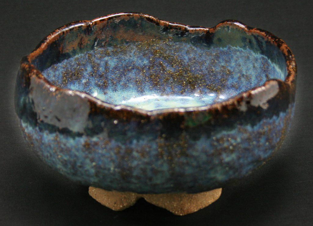 Rough-edged footed bowl in textured BRT clay with deep blue and brown glazes.