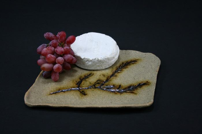 Another rustic cheese platter imprinted with a stem of rosemary