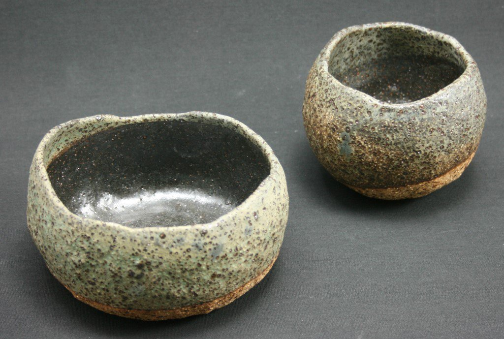 A pair of rustic green bowls in Tallaine's signature style of textured organic forms