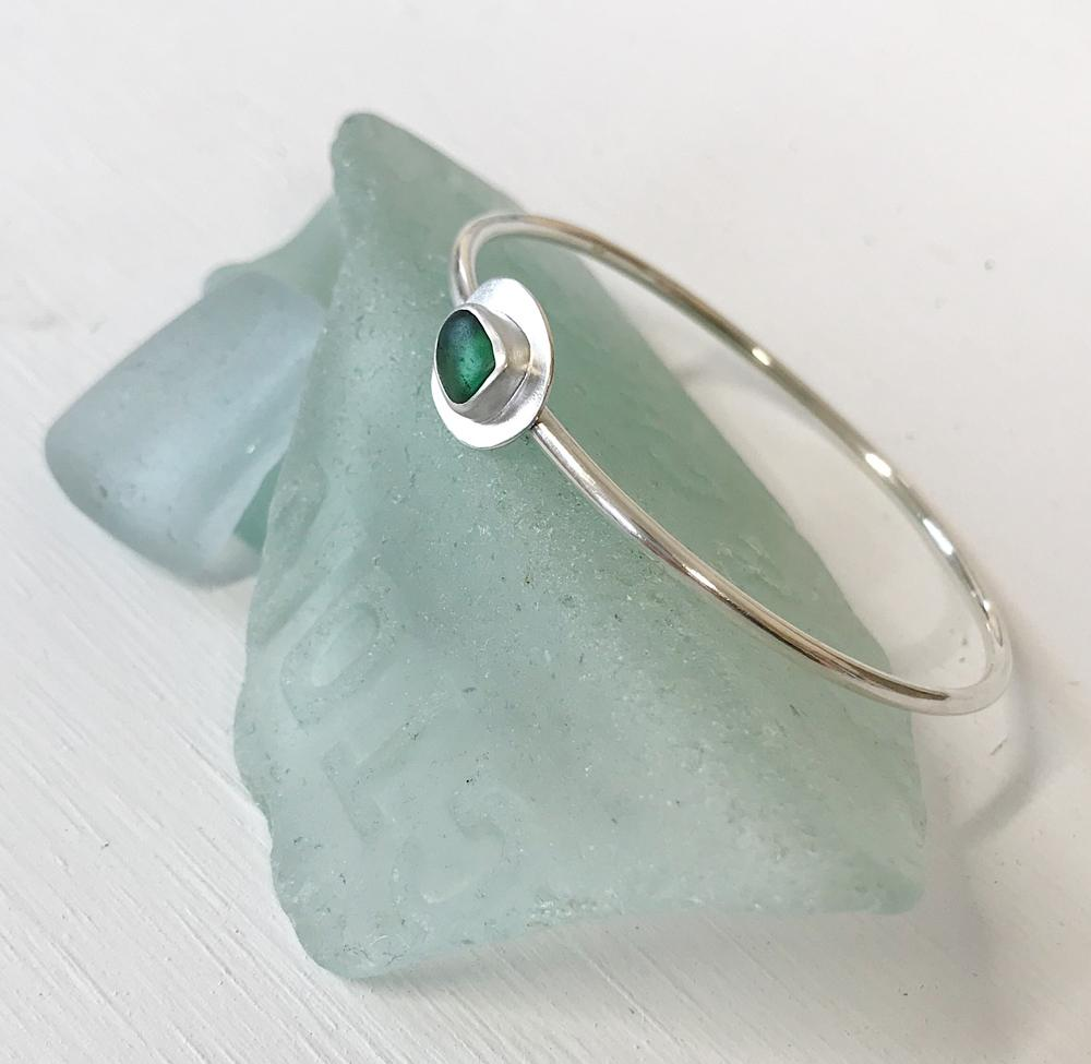 A silver bangle with an organic shaped centre setting of jade green sea glass, leaning on the well-worn remains of an old bottle