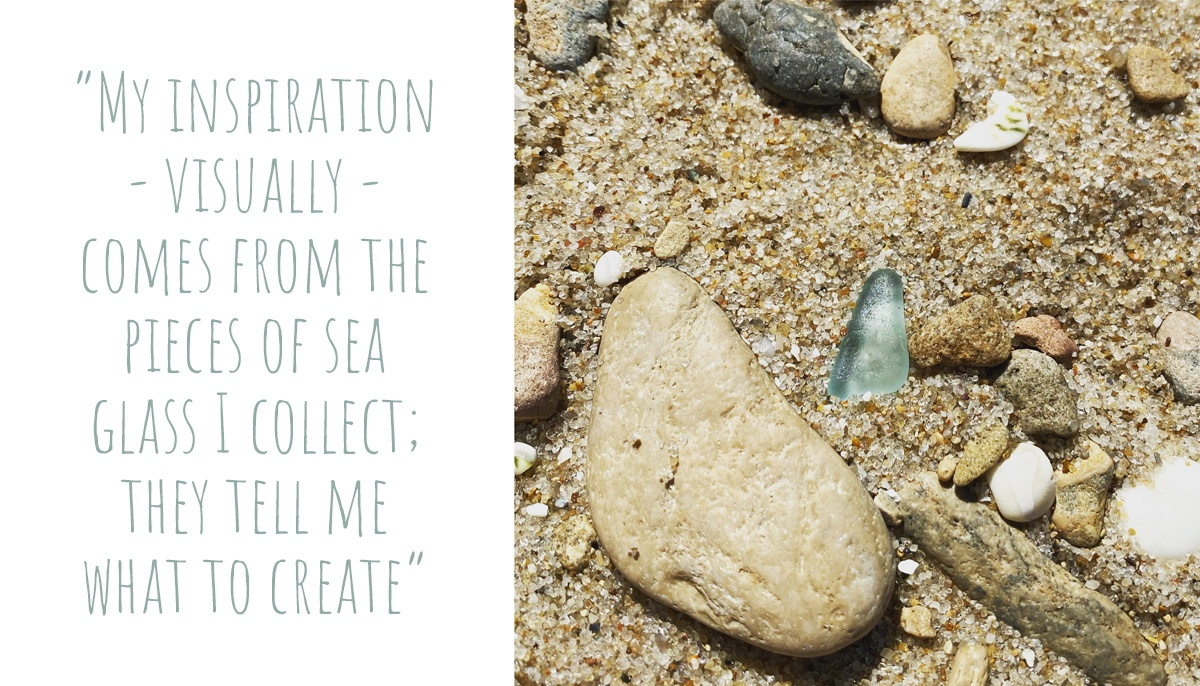 A piece of aqua seaglass uncovered in the sand amidst the rocks and shells; 'My inspiration – visually – comes from the pieces of sea glass I collect; They tell me what to create'