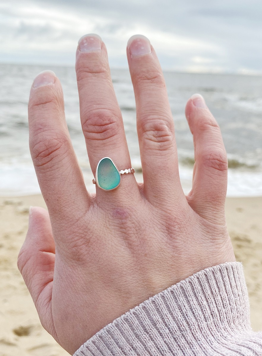 A delicate silver scalloped ring set with a large aqua green piece of sea glass worn on a hand in front of the ocean