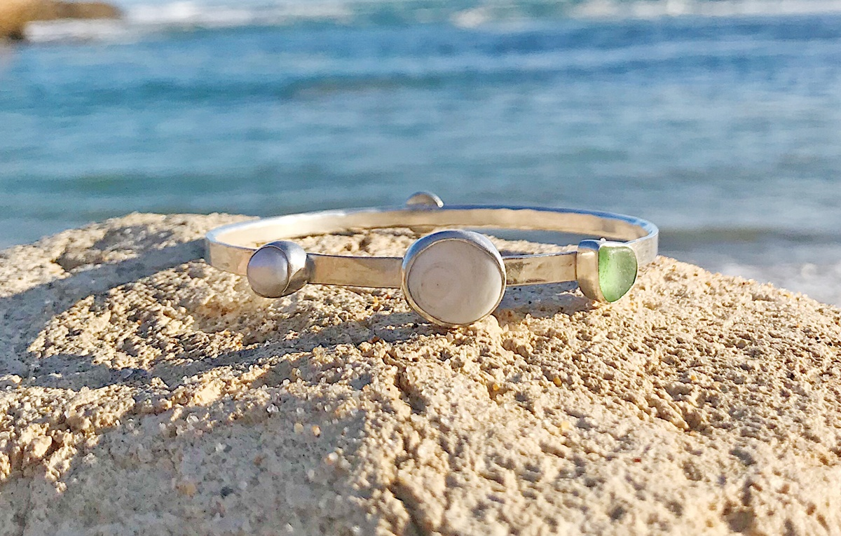 A Silver bracelet set with sea glass and sea pottery sitting on a rock in front of the ocean