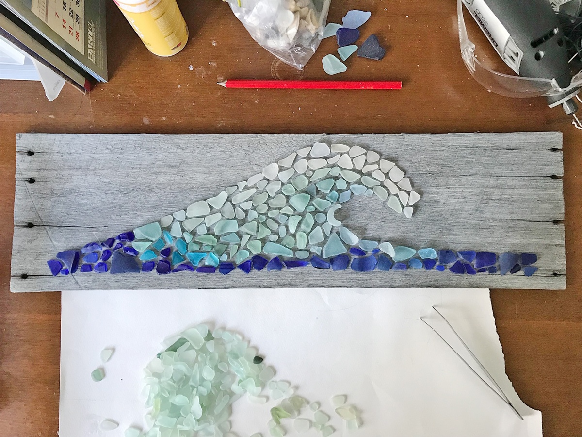 A sea glass collage of a wave coming together on recycled timber – each piece of sea glass is sorted by colour and shape, and hand selected to create gradients of colour