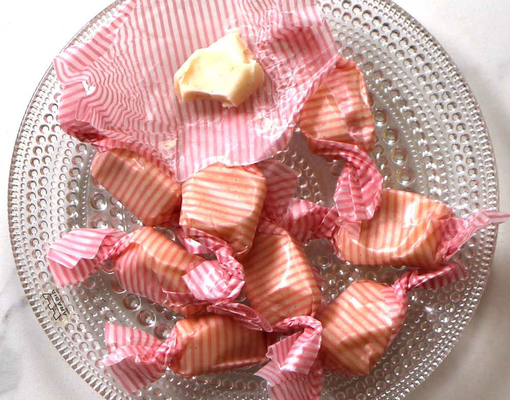 A glass plate of handmade vanilla bean taffy in striped candy wrappers