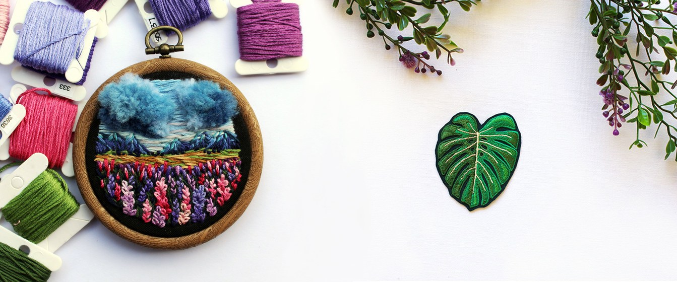 Hand embroidered mini hoop art of the New Zealand Highlands, and a monsterra leaf embroidered badge by Queensland maker, PatchHaven