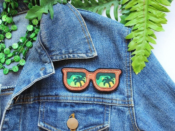 Denim jacket with embroidered iron-on patch depicting sunglasses with palm tree reflections