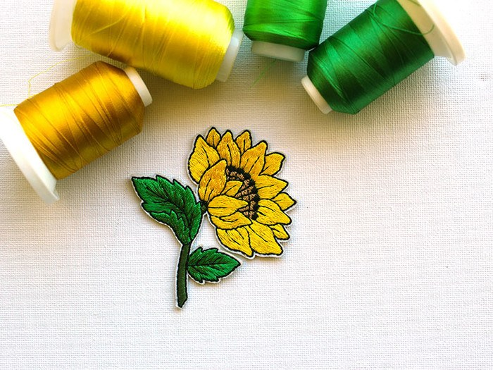 Machine embroidered sunflower iron-on badge by PatchHaven surrounded by rolls of golden and green thread