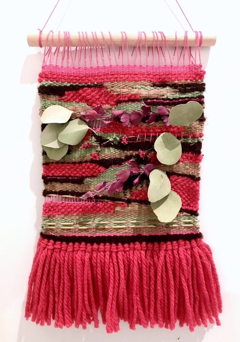 Pink woven wall-hanging with botanical elements by Pikaloo